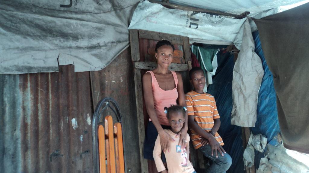Une femme, une petite fille et un garçon posent pour la photo devant une maison en bois