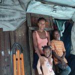 Une femme, une petite fille et un garçon proche comme une famille, posant sous un abri fait de métal et de tissus