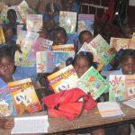 Un groupe d'enfant dans une salle de classe tenant des livres et des cahiers dans leurs mains