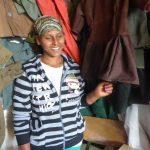 une femme entourée de vêtements, souriant