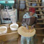 une femme assise, triant des graines. La concentration est au rendez-vous.
