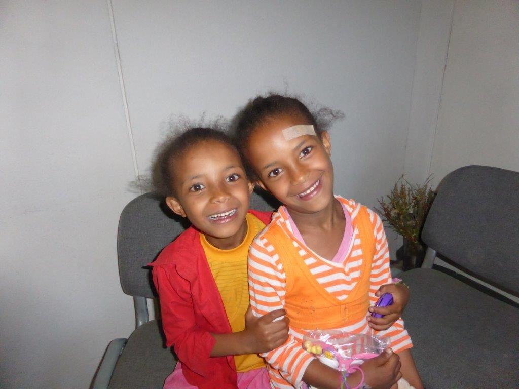 Deux petites filles, l'une sur les genoux de l'autre, sourient à l'appareil