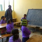 des enfants et un professeur dans une salle de classe, apprenant à compter