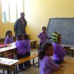 Enfants dans une salle de classe tenants des livres et cahiers dans leurs mains